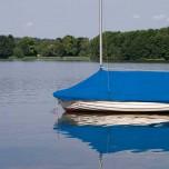 Blaues Boot mit Spiegelbild auf dem Schwielochsee
