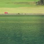 Rotes Auto mit grüner Wiese und grünem Bergsee
