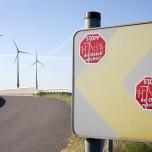 Protest-Aufkleber gegen Windräder mit Windrädern im Hintergrund
