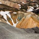 Farbliche Kontraste zwischen grauer Geröllhalde und bunten Bergen