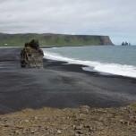 Steil aufragender Felsen am schwarzen Strand bei Dyrholaey