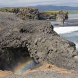 Dyrhólaey - Torbogen mit Gischt und Regenbogen, dahinter schwarzer Strand